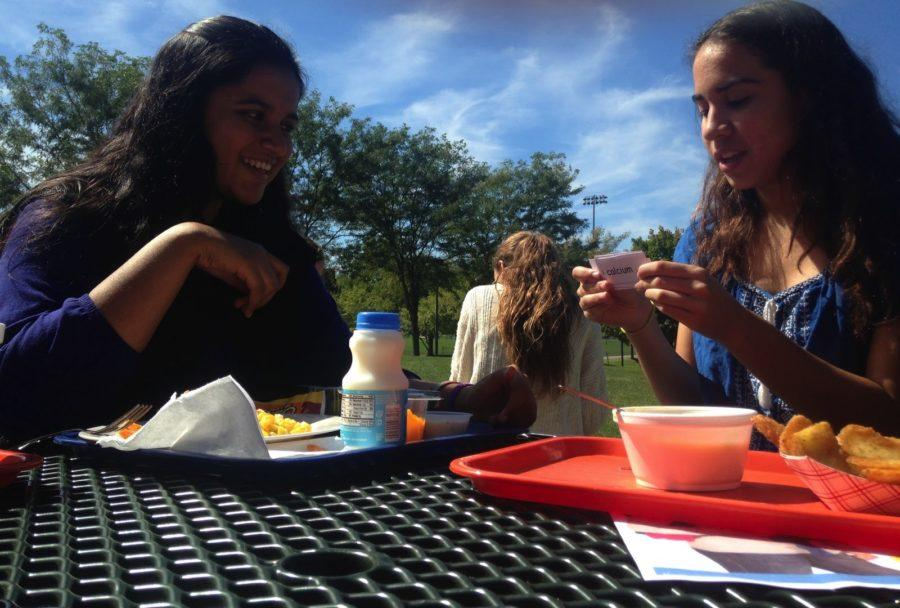 Sophomores Daniela Farias (right) and Fatima Asghar (left) study for a chemistry test on  November 23, 2015. Using flashcards to practice vocabulary, Farias and Asgar steal bites of lunch at Hershey High School, in Hershey, Pennsylvania.