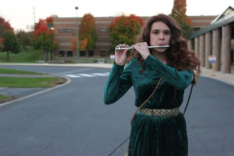 Emily Nothnagle plays her flute outside of HHS, on October 20th, 2015. Her 'Merida' costume was chosen because of the similarity between the characters hair, and Nothnagle's hair.