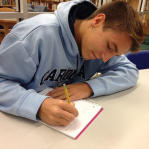 Junior Jake Hedrick writes in a journal on October 9, 2015. Hedrick has completed plenty of research on the Naval Academy.