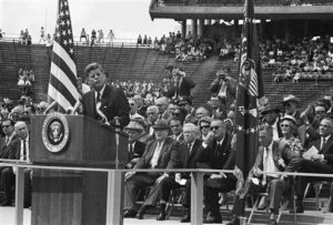 President John F. Kennedy delivers an address at Rice University stadium in Houston during his tour of NASA installations throughout the country, Sept. 12, 1962. The President promised that outer space will not be filled with weapons of mass destruction. Vice President Lyndon B. Johnson is sitting to the right of the President, wearing sunglasses. (AP Photo)