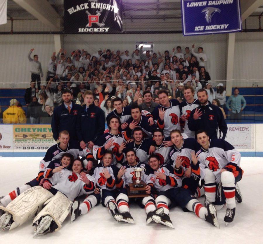 Hershey Boys hockey team pose for a picture featuring the Merriman-Weare cup, and the Hershey High Student section. The Trojans have won the cup for four years in a row (photo courtesy of Hershey Boys Ice Hockey twitter @Hershey_Hockey)