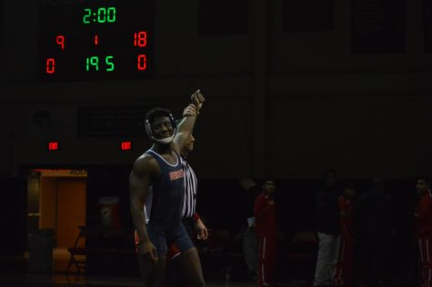 Senior J'Michael Wedderburn smiles while getting his hand raised to unexpected  forfeit in the 195lb weight class. Trojans beat Susquehanna 38-36.