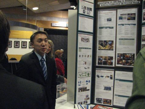 """Junior Alan Hwang explains his project, entitled """"iOS App: Enable an Aruduino-Controlled 3D Printed Hand,"""" to onlookers. Hwang was awarded Grand Champion of the Capital Area Science & Engineering Fair for his work. (Broadcaster/Emily Briselli)"""