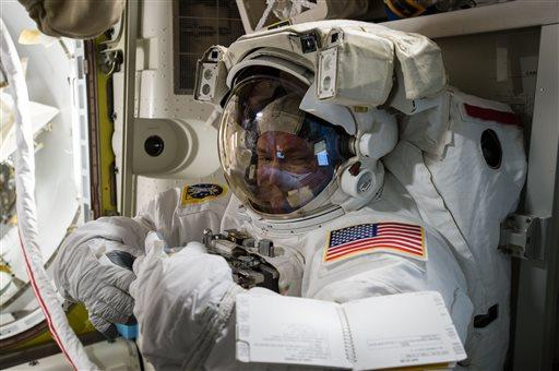In this photo provided by NASA and posted on Twitter on October  26, 2015, astronaut, Scott Kelly, tries on his spacesuit inside the U.S. Quest airlock of the International Space Station. NASA opened its astronaut-application website Monday, December 14, 2015. It's accepting applications through February 18, 2016 (NASA via AP).