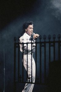 """American pop star Prince sings at the beginning of his second concert around July 10,1988 at Paris Bercy stadium, where he began his """"Lovesexy"""" world tour.(AP Photo/Pierre Gleizes)"""