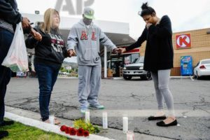 Francine Prieto-Estrada, left, leads Donald Pride and Elisa Castro in a prayer at memorial site for the gunned-down 12-year-old at Circle K gas station on Highland Avenue and Orange Street in San Bernardino, Calif., on Monday, March 14, 2016. The 12-year-old was shot and killed late Sunday, and a 14-year-old was wounded in the same shooting. (Rachel Luna/San Bernardino Sun via AP)