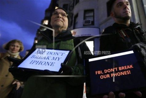 Demonstrators Peter Brockmann, of Northborough, Mass., center, and Chris Gladney, of Boston, right, display iPads with messages on their screens outside an Apple store, Tuesday, Feb. 23, 2016, in Boston. Demonstrators are expected to gather in a number of cities Tuesday to protest the FBI obtaining a court order that requires Apple to make it easier to unlock an encrypted iPhone used by a gunman in December's mass murders in San Bernardino, Calif.. (AP Photo/Steven Senne)