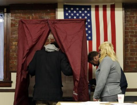 Dan Cunningham, left, enters a voting booth to cast his vote at Hoboken City Hall, Tuesday, Nov. 8, 2016, in Hoboken, N.J. (AP Photo/Julio Cortez)