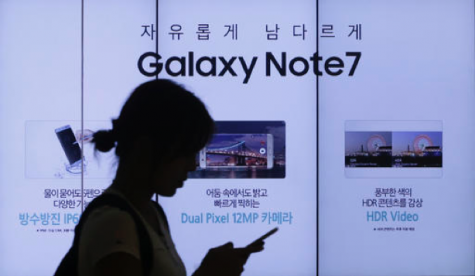 In this Friday, Sept. 2, 2016, file photo, a woman walks by an advertisement of the Samsung Electronics Galaxy Note 7 smartphone at the company's showroom in Seoul, South Korea. The Federal Aviation Administration said Thursday night, Sept. 8, 2016, that because of recent fire reports involving the Galaxy Note 7 smartphone, passengers shouldn't use or charge one or stow one in checked baggage. The three biggest U.S. airlines: American, Delta and United, said Friday that they were studying the FAA warning but it was unclear how they would make sure that passengers keep the Samsung devices powered off. (AP Photo/Ahn Young-joon, File)