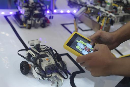A student prepare his robots to participate in First Lego League competitions, during a largest competition on technology innovation in Brasilia, Brazil, Thursday, Nov. 10, 2016. The knowledge olympiad, which takes place every two years, is considered the largest competition of the type in Latin America, with more than 1,200 students taking part in challenges and technological competitions. (AP Photo/Eraldo Peres)