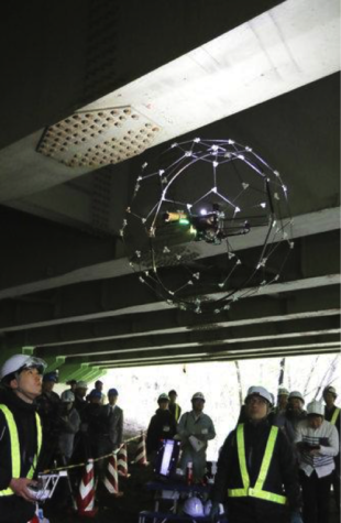 A drone lights up and takes photos while flying in a dark and narrow space under a bridge at Sendai City, Miyagi prefecture on May 16, 2017. Kazunori Ohno, Japanese Assistant Professor of Tohoku University and his team developed a drone which doesn't fall even colliding with something like bridge. Drone is guarded with football-shape device (96cm diameter, 2.6kg), made of strong and special material, can fly stable even it bumping into a building or other things. ( The Yomiuri Shimbun via AP Images )