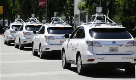 In this May 13, 2014, file photo, a row of Google self-driving cars stands outside the Computer History Museum in Mountain View, Calif. Google has spent six years working on cars that can drive without human assistance. But the company says it doesn't want the responsibility of building the robotic vehicles. (AP Photo/Eric Risberg, File)