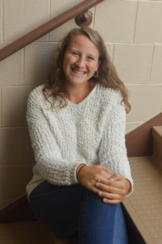 Junior Elizabeth Newman poses for a quick picture to show off  her stylish sweater for this season. Newman shows off her comfy white sweater with a pair of jeans and hoop earrings. (Broadcaster/Elaina Joyner)
