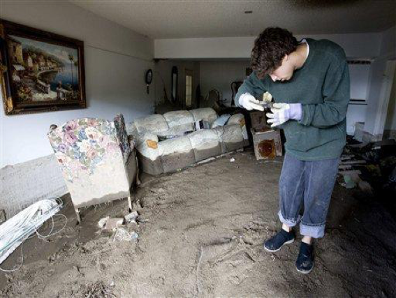 Unable to stand upright due to large amounts soil covering the floor, Brian Laguna recovers personal belongings after a mudslide caused by heavy rains damaged his house in La Canada Flintridge, Calif. on Monday, Feb. 8, 2010. Another storm is expected to hit the Los Angeles area Tuesday. (AP Photo/Hector Mata)
