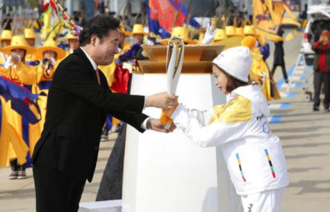 South Korean Prime Minister Lee Nak-yon, left, passes an Olympic torch to torch bearer, South Korean figure skater You Young, at Incheon Bridge in Incheon, South Korea, Wednesday, Nov. 1, 2017. The Olympic flame arrived in South Korea on Wednesday where it will be passed throughout the country by thousands of torchbearers on a 100-day journey to the opening ceremony of the 2018 Winter Olympics in Pyeongchang. (AP Photo/Lee Jin-man)