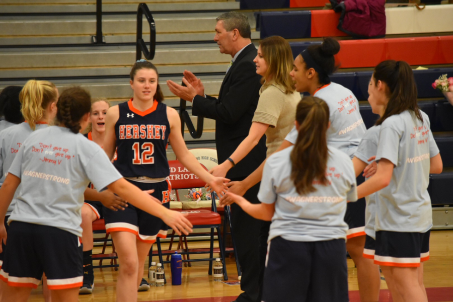 HHS senior Maggie Miller high-fives her teammates as she runs on the court. Miller received Athlete of the Month for contributing to the Girls Basketball Mid-Penn Conference with 5 steals and ending her career with 199 points this season. (Courtesy of Deanna Zugay)