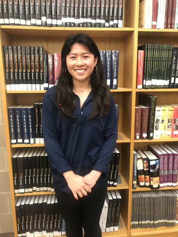 Jenny Kim, HHS senior, poses in the HHS library after being named April Student of the Month. She plans on attending the University of Virginia to study neuroscience and art. (Broadcaster/ Claire Sheppard)