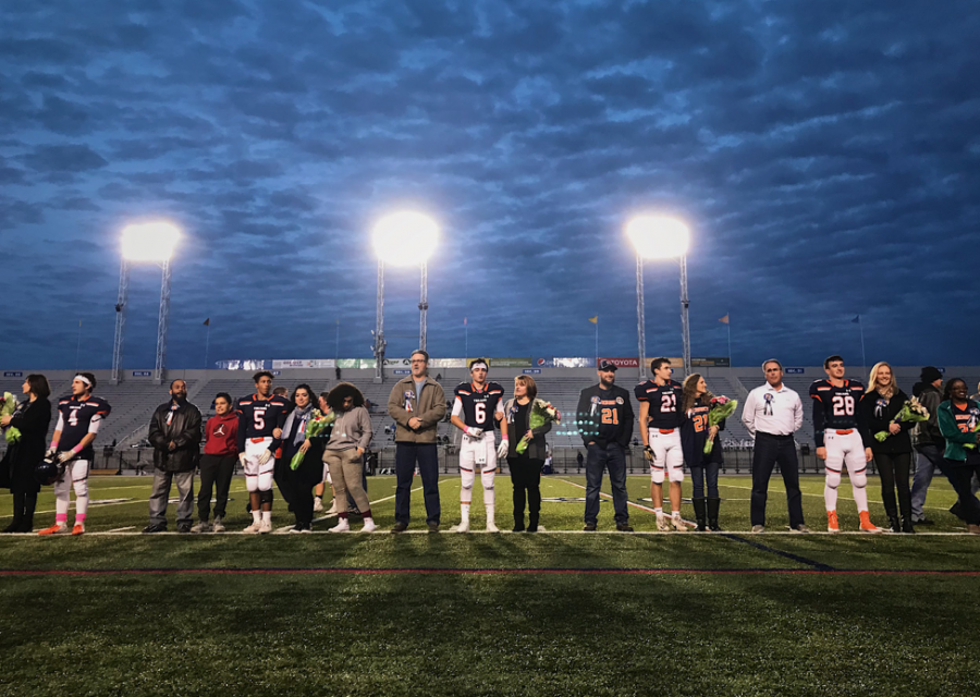 HHS Football players stand on the field with their family and friends after receiving recognition for their dedication to the team before kick off. The Trojans were defeated by the Falcons with a final score of 42-25 on Friday, October 19, 2018. (Broadcaster/Kate Clark)