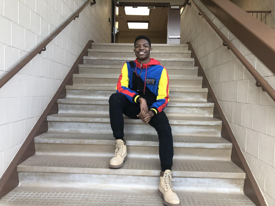 Junior+Akiva+Brooks+sitting+on+the+stairs+in+his+90s+inspired+outfit.+Bright+colored+jackets+were+a+staple+piece+in+the+90s%2C+and+now+has+been+made+popular+again+in+2018.%28Ashlyn+Weidman%2F+The+Broadcaster%29