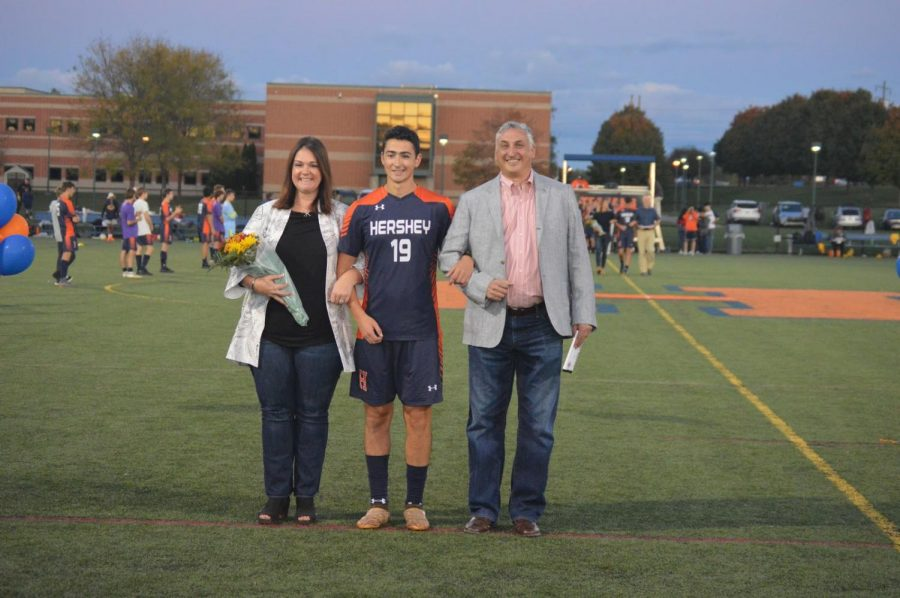 Alex Berger being escorted by his parents on senior night. This is the first year Berger has played for the school since moving here during sophomore year, due to his commitment to elite club teams. (Broadcaster/Leah Koppenhaver)