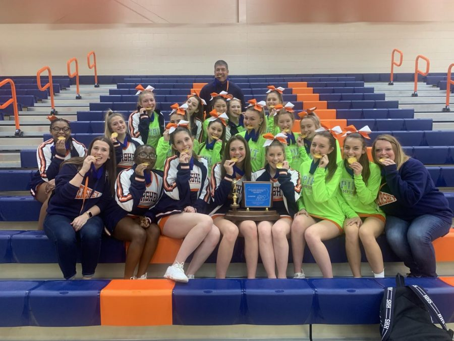 The HHS Cheer team smiles with their medals, the District trophy and DTSD Athletic Director Scott Govern on Saturday, December 7, 2019. The team will compete at States on January 10th and 11th, 2020. (Broadcaster/Caroline Glus)