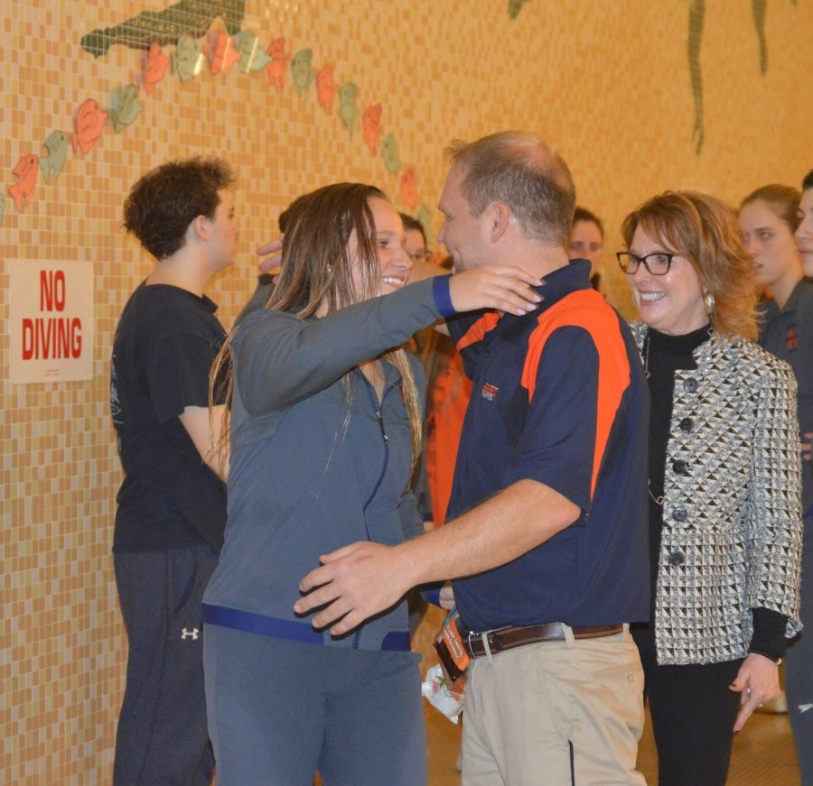 Senior Jillian Ruddle embraces coach Greg Fastrich who has been coaching for over 20 years. Ruddle has been swimming for 13 years. (Katie Jones/Broadcaster)