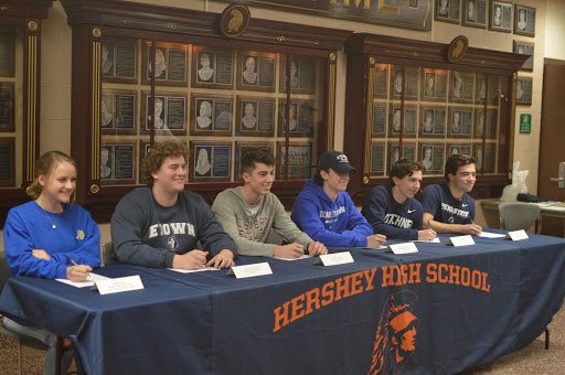 From+left+to+right%2C+Katie+Jones%2C+Colin+Kondracki%2C+Ian+McDonald%2C+Alec+Newman%2C+Evan+Walters%2C+and+Adam+Wildasin+smile+as+they+prepare+to+sign+their+commitments+to+their+college+of+choice.+%28Broadcaster%2F+Paige+Dalto%29