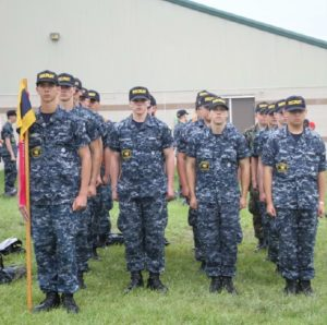 Mark Suminski, far left holds the guidon during role call at Sea Cadets on June 10, 2015. The flag's colors represent the division Suminski is in.