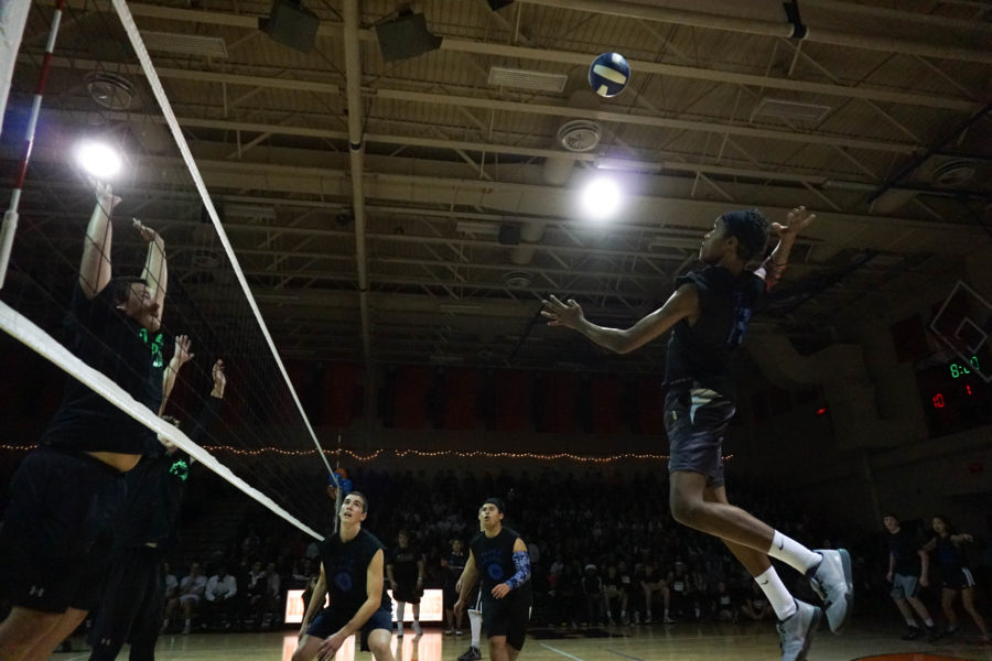 Junior Moses Kresch jumps up to hit the ball against two blockers on team Attack Pack in the quarterfinals.