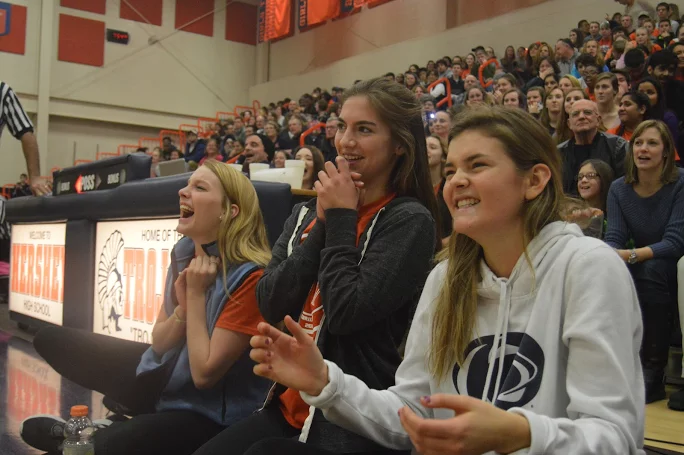 Left+to+right%3A+Katie+Sweigart%2C+Maddie+Donahue%2C+and+Grace+Miller+laugh+courtside+at+the+halftime+entertainment.+%28Broadcaster%2FBella+D%E2%80%99Adderio%29%0A