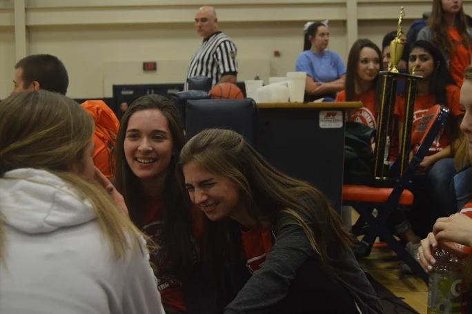 HHS+Senior+Maddie+Donahue+laughs+courtside+with+Shaye+Carver+during+halftime+of+the+teachers+vs.+teachers+basketball+game+against+LD.+%28Broadcaster%2FBella+D%E2%80%99Adderio%29%0A