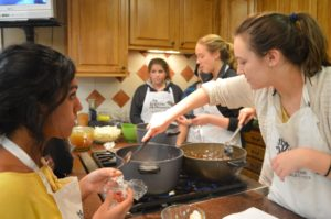 Becca Hetrick (far right) stirs the soup she's making as Millika Kodavataganti (far left) watches her; behind them, Victoria Corado (center) and Emily Liesch (left of Hetrick) work on the cream of cauliflower soup on January 21st, 2016. All four of them were excited to eat their meals afterwards.