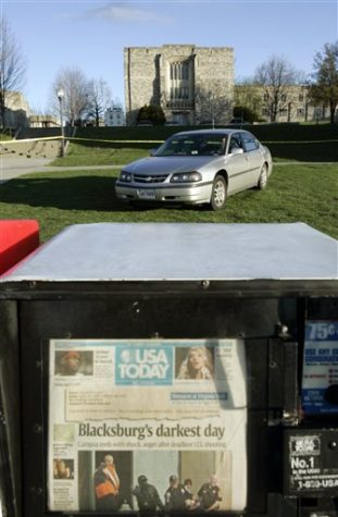 A newspaper vending machine shows a headline of Monday's shooting as a security guard sits in his car outside Norris Hall on the campus of Virginia Tech University in Blacksburg, Va., Tuesday, April 17, 2007. A gunman killed some 30 students and others in the hall during a rampage on Monday that left a total of 33 dead. (AP Photo/Steve Helber)