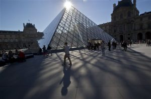 A man passes by the glass-pyramid of the Louvre museum in Paris, France. The City of Light is not only one of Europe's most beautiful cities it's also the perfect size for exploring on foot. (AP Photo/Michel Euler, File)