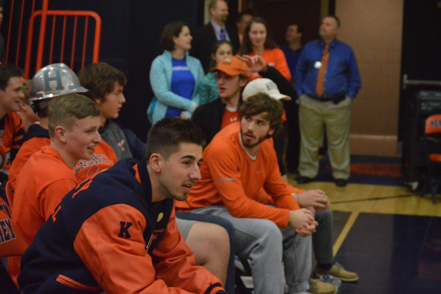 Seniors Vincent Paioletti, Brendan Twaddell, and Daniel Ioffreda sit on the teachers bench and watch as students participate in the half court shot competition during halftime.  (Broadcaster/ Kaylee Williams)
