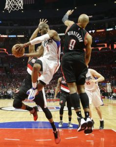 Los Angeles Clippers' Chris Paul, center, passes the ball under pressure by Portland Trail Blazers' Gerald Henderson, right, and Maurice Harkless in the second half in Game 1 of a first-round NBA basketball playoff series, on Sunday, April 17, 2016, in Los Angeles. The Clippers won 115-95. (AP Photo/Jae C. Hong)
