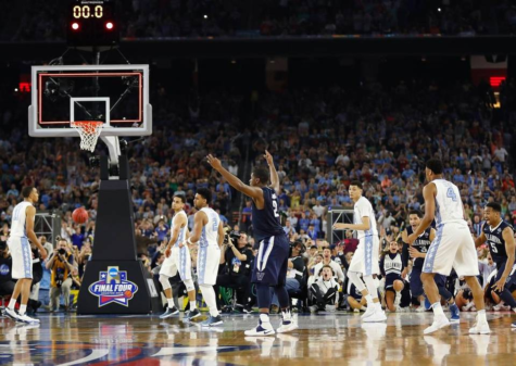 Kris Jenkins, center,  of Villanova celebrates among a group of stunned North Carolina players following his buzzer-beating jump shot. The Villanova Wildcats beat the UNC Tar Heels 77-74 on Monday April 4, 2016. (AP/David J. Phillip)