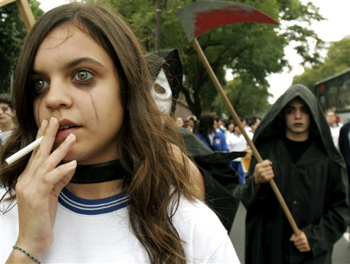 Paraguayan student Paulina Velazquez, left, of the Adventist School , pretends to smoke during a No-Tabacco march on World No Tobacco Day in downtown Asuncion, Paraguay, Wednesday, May 31, 2006. The World Health Organization said smoking is the single biggest preventable cause of death worldwide, claiming 4.9 million lives a year. (AP Photo/Jorge Saenz)