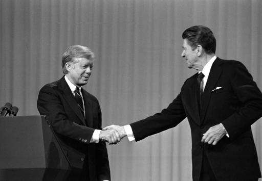 "In this Oct. 28, 1980 file photo, President Jimmy Carter shakes hands with Republican Presidential candidate Ronald Reagan after debating in the Cleveland Music Hall in Cleveland. The fall debates are always a big part of any presidential campaign. But with many 2016 voters underwhelmed by both Hillary Clinton and Donald Trump, this year's debates could well be more influential than usual. In 1980, a cheerful Reagan shone in his debate against Carter, scolding him with a gentle ""There you go again,"" and posing a pointed closing question: ""Are you better off than you were four years ago?"" (AP Photo/Madeline Drexler, File)"