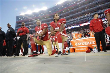 San Francisco 49ers safety, Eric Reid (left kneeling), and quarterback, Colin Kaepernick (right kneeling), do not stand for the National Anthem before their game against the Los Angeles Rams on September 12th, 2016, in Santa Clara, California. (AP Photo/Marcio Jose Sanchez)