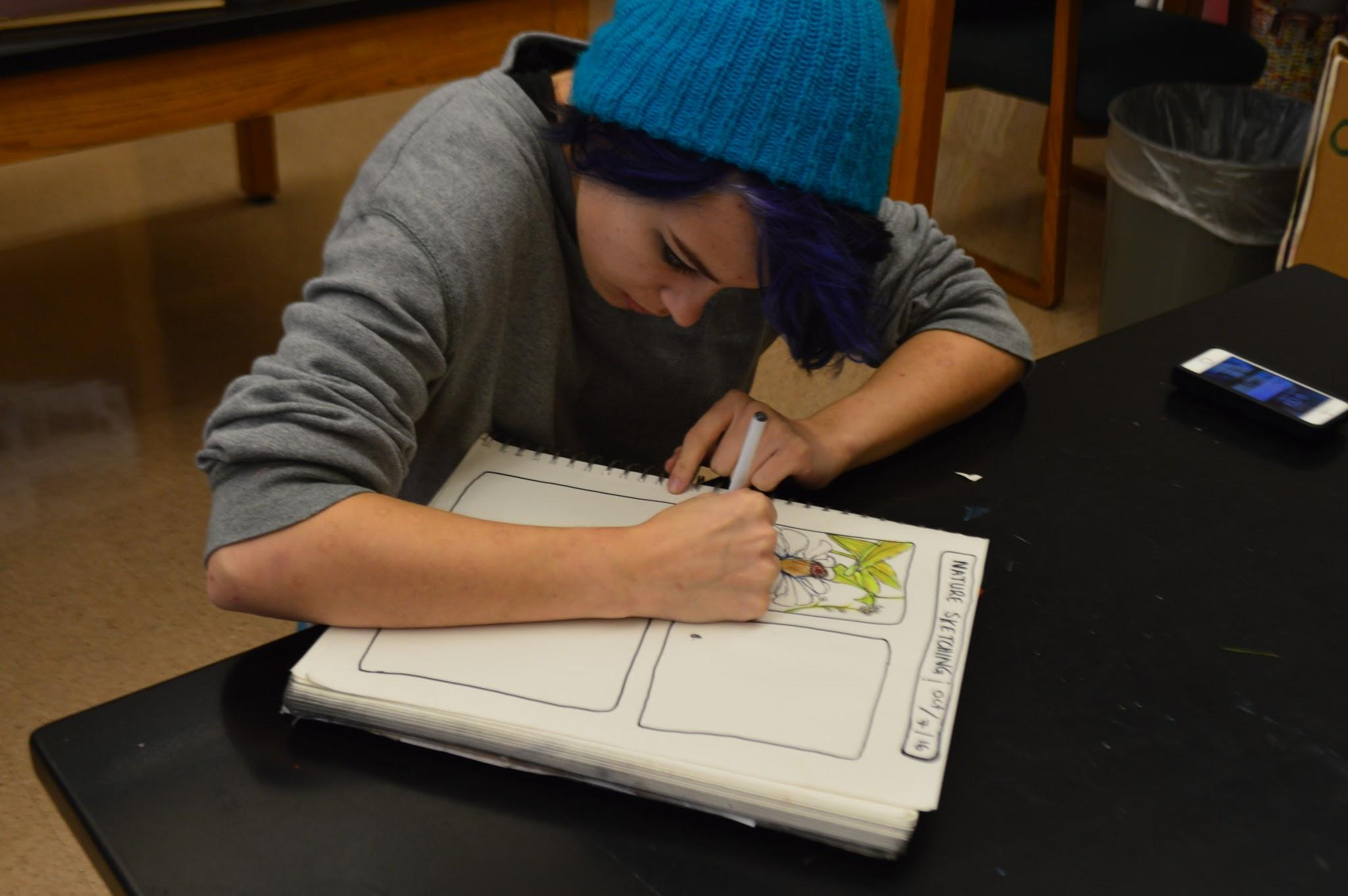 On October 7th, 2016, HHS had its annual Community Day. Pictured above, Jayden Solovey finishes up her drawing of the high school's garden in the nature sketching session. (Broadcaster/ Madison Held)