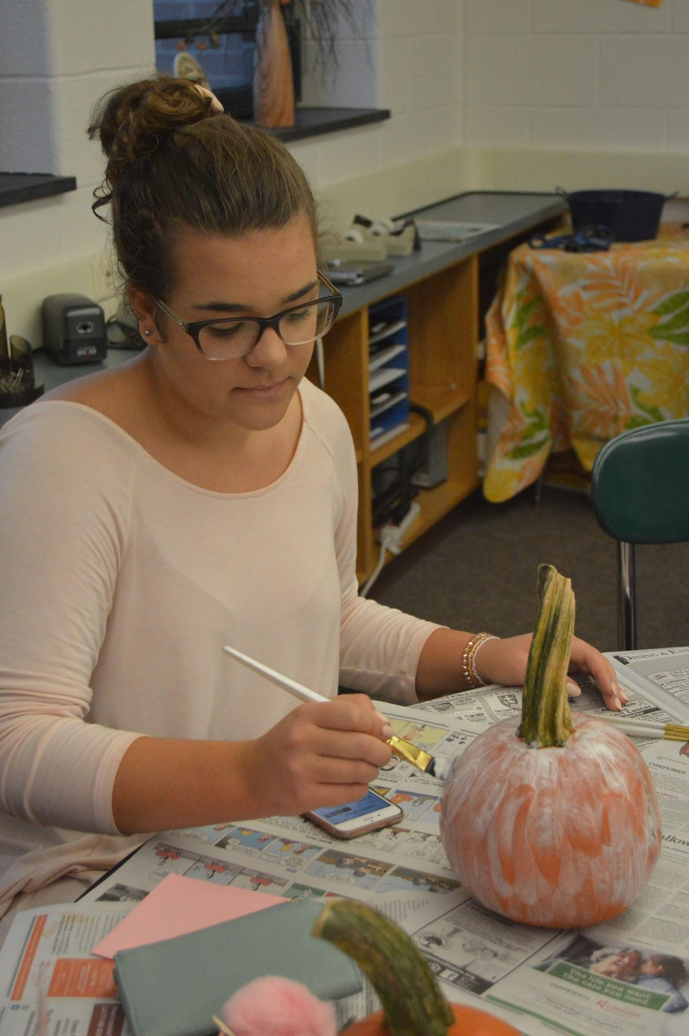 Rachel Haines paints pumpkins at Hershey High School on October 7th, 2016.  Community day brought students together through different sessions they could sign up for. (Broadcaster/ Elaina Joyner)