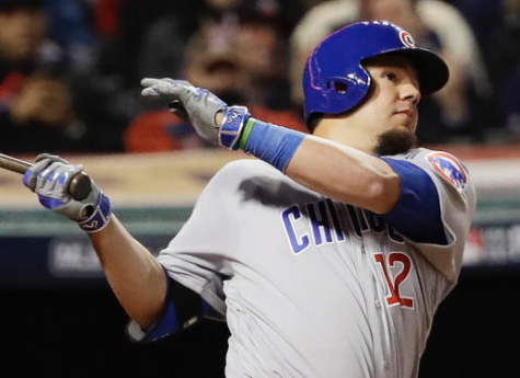 In this Tuesday, Oct. 25, 2016, photo, Chicago Cubs' Kyle Schwarber, wearing a green wristband on his left arm, hits a double during the fourth inning of Game 1 of the Major League Baseball World Series against the Cleveland Indians in Cleveland. (AP Photo/David J. Phillip)
