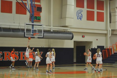 Sophomore Kate Sinz, left, makes a shot while warming up with her team. The Trojans Girls' Basketball Team warmed up to prepare for the second half of their game against Palmyra. (The Broadcaster/ Camille Heck)