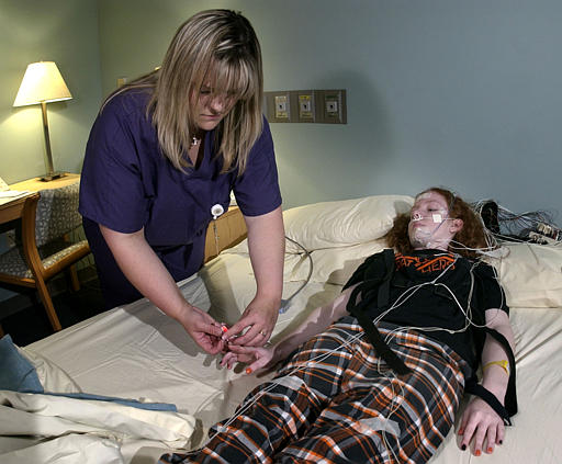 Polysomnographic specialist Kyndra Vanderheyden, left, connects sensors to Cara Horton, 16, as Horton prepares to spend the night at the Sleep Disorders Center at St. Lukes Hospital in Kansas City, Mo., Sunday, Oct. 3, 2004. Horton is among a growing number of teens suffering from insomnia or other sleep disorders. (AP Photo/Charlie Riedel)