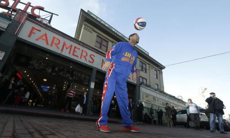 Harlem Globetrotter Buckets Blakes showing off his ball-handling skills on Tuesday, February 9th, 2016, in front of a famous Seattle market for Pike. Blakes did not set a record this year; however, he does hold the record for most amount of underhand half-court shots in one minute. (AP Images/ Ted S. Warren)