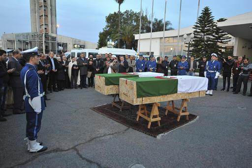 In this photo dated Saturday, Feb. 4, 2017, officials and relative of Abdelkrim Hassane and Khaled Belkacemi, stand around their flag-draped coffins during a ceremony held at Houari Boumediene airport in Algiers, Algeria. Hassane and Belkacemi were two of the six victims of the Quebec City mosque shooting. (AP Photo/Sidali Djarboud)