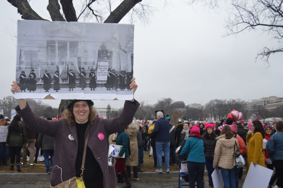 A+woman+shows+off+a+sign+depicting+the+original+suffragettes+in+front+of+the+White+House.+The+end+point+of+the+march+was+The+White+House+where+thousands+gathered+to+send+a+message+to+President+Donald+Trump.+%28Broadcaster%2F+Emily+Liesch%29+