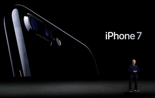 In this Sept. 7, 2016, file photo, Apple CEO Tim Cook announces the new iPhone 7 during an event to announce new products, in San Francisco. Though owners of last year's iPhones might not need to rush out to get the iPhone 7 or 7 Plus, those clinging on to older models might find enough cumulative improvements from the past two years, including sharper photos at 12 megapixels, introduced last year. (AP Photo/Marcio Jose Sanchez, File)