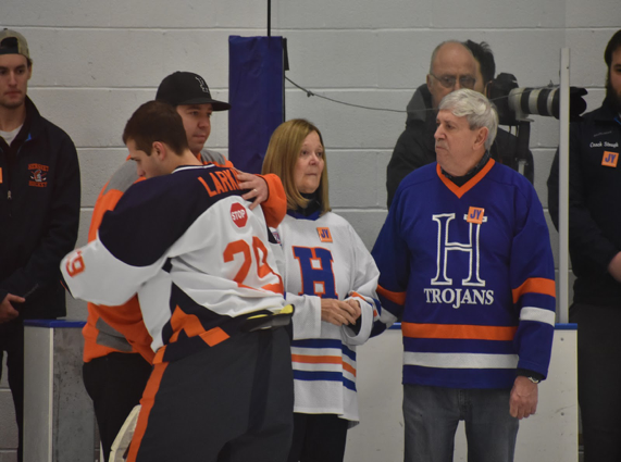 Wednesday, January 18th, Freshman Chris Larkin hugs Yingling's brother, Jordan Yingling, with parents Jane and Jack Yingling, after a pre-game ceremony before playing the Cedar Crest game. Hershey ended up winning the game 9-1. (Broadcaster/Mallory Drayer)